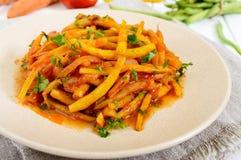 青豆辣温暖的沙拉在西红柿酱的在白色木背景的一块板材 库存照片
