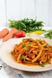 青豆辣温暖的沙拉在西红柿酱的在白色木背景的一块板材 免版税图库摄影