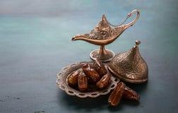 青铜盘与日期和在深绿木背景的aladdin灯 ramadan的背景 ramadan的kareem 库存图片