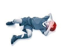 青年亚裔足球运动员顶视图以痛苦在前额 库存照片