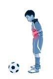 青年亚洲足球运动员stomachache 充分机体 免版税库存照片