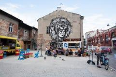 青年人吃午餐在有好的街道艺术的墙壁附近 免版税库存照片