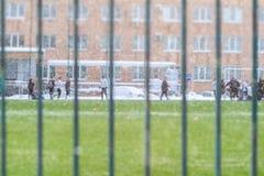 青年人在冬天踢在雪的橄榄球在他的房子庭院里  视图通过范围 活跃户外运动 免版税库存图片