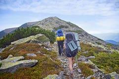 青年人在喀尔巴阡山脉步行夏令时 免版税库存照片