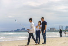 青年人在岘港使用在中国海滩的selfie棍子 库存照片
