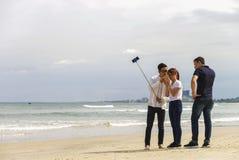 青年人在岘港使用selfie棍子iat中国海滩 免版税库存图片