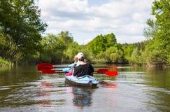 青年人在美好的自然的一条河划皮船 蝴蝶日草夏天晴朗的swallowtail 库存照片