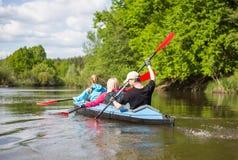 青年人在美好的自然的一条河划皮船 蝴蝶日草夏天晴朗的swallowtail 库存图片