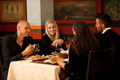 青年人在餐馆吃海鲜晚餐并且喝酒 免版税库存图片