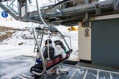 青年人坐与位子的滑雪电缆车在滑雪手段 免版税库存照片
