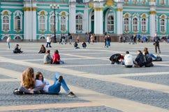 青年人基于宫殿正方形,圣彼德堡,俄罗斯 图库摄影