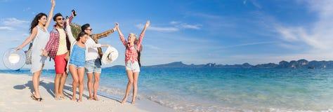 青年人小组海滩暑假,愉快的微笑的朋友走的海边 免版税库存图片