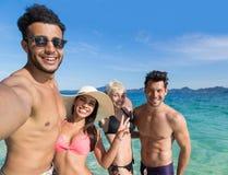 青年人小组海滩暑假,拍Selfie照片的两个夫妇愉快的微笑的朋友 图库摄影