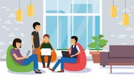 青年人谈论和与坐在五颜六色的辎重袋的膝上型计算机和片剂一起使用 免版税库存图片