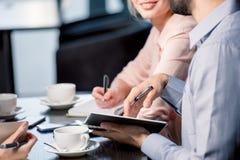 青年人饮用的咖啡和写在笔记本在业务会议,工作午餐概念上 免版税库存图片