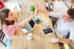青年人高fiving在会议上在咖啡馆 免版税库存图片