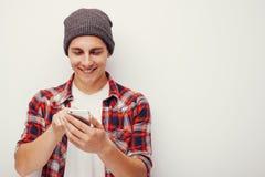 青年时期和技术 使用巧妙的电话的人演播室画象  查出 库存照片