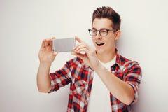青年时期和技术 使用巧妙的电话的人演播室画象  查出 免版税库存图片