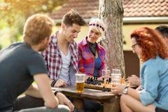 青年时期获得下棋的乐趣在木头 免版税库存照片