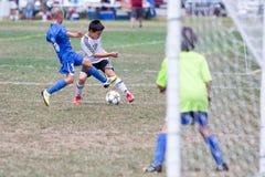 青年足球为球的足球运动员战斗 免版税库存图片