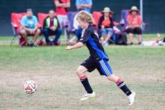 青年足球跑与球的足球运动员 免版税库存照片