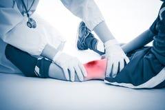 青年足球运动员膝盖痛苦,在白色背景 医生perfo 免版税库存图片