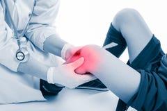 青年足球运动员膝盖痛苦,在白色背景 医生perfo 免版税库存照片