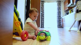 静态射击,逗人喜爱的七个月使用与在地板愉快的童年,早期的发展的教育玩具的男婴 股票录像