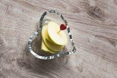 静物画为华伦泰` s天 果子切片在木串的苹果有在一个水晶花瓶的心脏的以心脏的形式, 库存图片