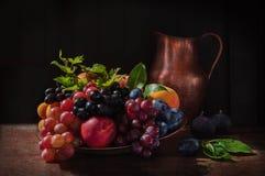 静物画用果子:葡萄、苹果、无花果、梨和桃子在近古色古香的铜镀锡铁皮和木桶匠水罐 免版税库存图片