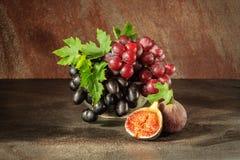 静物画用果子:葡萄,在古色古香的铜罐子杯子的无花果 免版税图库摄影
