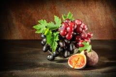 静物画用果子:葡萄,在古色古香的铜罐子杯子的无花果 免版税库存图片