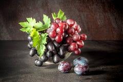静物画用果子:葡萄,在古色古香的铜罐子杯子的李子 图库摄影
