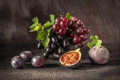 静物画用果子:葡萄,无花果,在古色古香的铜罐子杯子的李子 免版税库存照片