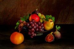 静物画用果子:葡萄,苹果,无花果,在古色古香的铜镀锡铁皮的梨 免版税库存图片
