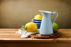静物画用柠檬和蓝色搪瓷水罐 库存图片