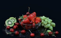 静物画用绿色葡萄、猕猴桃、樱桃和草莓 免版税库存图片