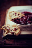 静物画用蔓越桔曲奇饼和在书的樱桃橘子果酱 免版税图库摄影