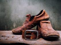 静物画老皮鞋和传送带 它更多肮脏和sha 库存图片