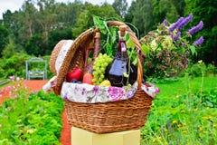 静物画:酒、葡萄、花和菜在篮子o 免版税库存照片