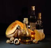 静物画;南瓜,核桃,在黑暗的背景的被装瓶的油 库存图片
