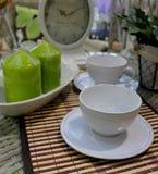 静物画-在与葡萄酒时钟和装饰绿色蜡烛的一张桌上安排的咖啡杯 免版税库存图片