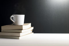 静物画-一个杯子在书的热的咖啡 图库摄影