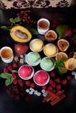 静物画不同的类型冰淇凌桃红色黄色白色,莓,芒果,西番莲果,香料,桂香,八角,美丽, a 免版税库存照片