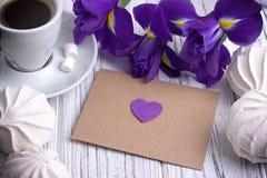 静物画与包围心脏标志在白色木背景的虹膜花 婚姻 图库摄影