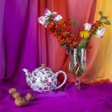 静物画与花束夏天开花,茶壶和核桃 免版税库存图片
