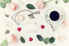 静物画-咖啡,桃子玫瑰,空插件,猫头鹰塑造了时钟,在白色背景的心形的糖果 库存图片