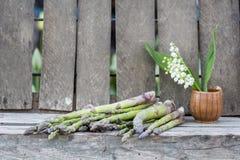 静物画构成用芦笋和陶瓷罐有铃兰的开花 免版税库存照片