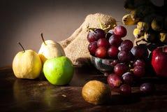 静物画结果实用中国梨、猕猴桃、红色苹果、葡萄和古芝 免版税库存图片