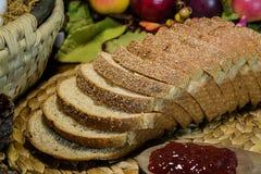 静物画棕色整个五谷面包和果酱 库存照片